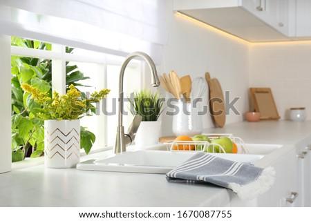 Beautiful white sink near window in modern kitchen #1670087755