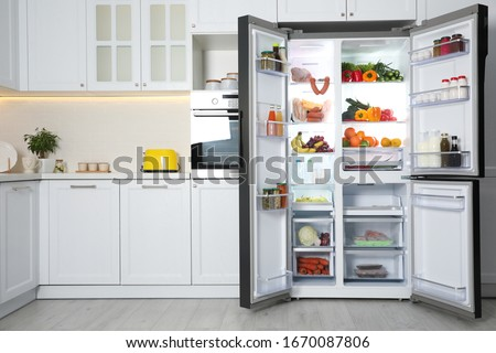 Open refrigerator filled with food in kitchen #1670087806