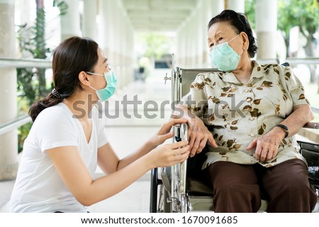 Young Asian grandchild taking care her grandmother sitting on wheelchair. Grandmother almost 90 years old was take care by her granddaughter while traveling at park. People wearing protective mask. #1670091685