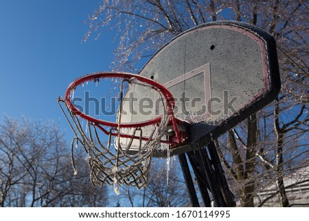 Horizontal low angle view of broken outdoor basketball hoop encased in ice after ice storm seen during a sunny morning, Quebec City, Quebec, Canada