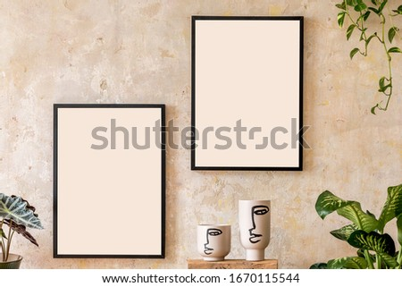 Interior design of living room with two black mock up poster frames, shelf, vases, plants and elegant personal accessoreis in wabi sabi concept.
