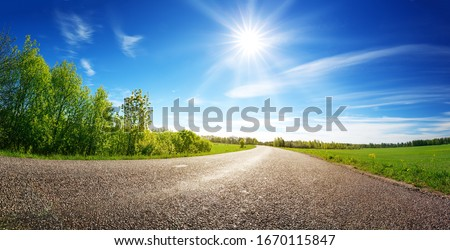 asphalt road panorama in countryside on sunny spring day Royalty-Free Stock Photo #1670115847
