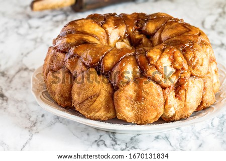 Easter dessert of Pull Apart Carrot Cake Monkey Bread. A yeast bundt cake made with cinnamon, carrots, nuts and a brown sugar glaze. Selective focus with blurred foreground and background.