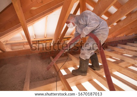 Worker with a hose is spraying ecowool insulation in the attic of a house. Insulation of the attic or floor in the house #1670187013