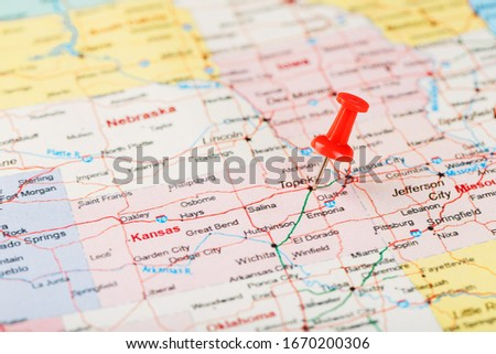 Red clerical needle on a map of USA, Kansas and the capital Topeka. Close up map of Kansas with red tack #1670200306