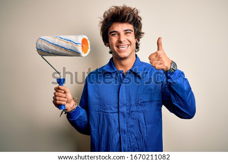 Young handsome painter man holding roller wearing uniform over isolated white background happy with big smile doing ok sign, thumb up with fingers, excellent sign