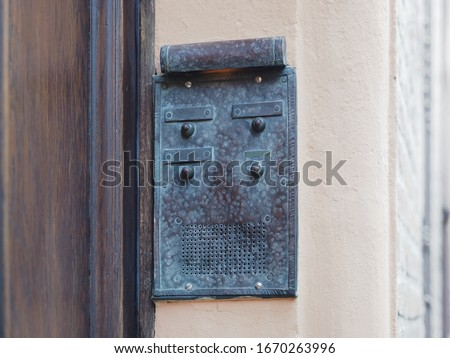 Vintage intercom next to the front door of a building. #1670263996