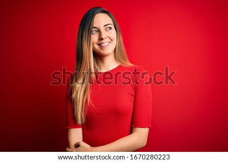 Young beautiful blonde woman with blue eyes wearing casual t-shirt over red background looking away to side with smile on face, natural expression. Laughing confident.