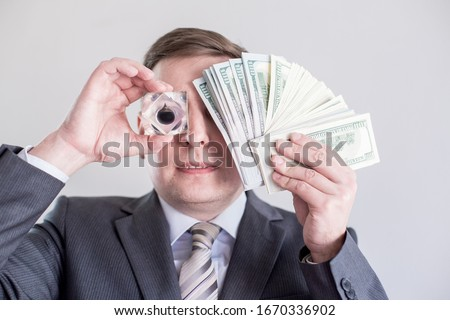 Businessman in suit holds in hands,looks to drop of black oil of Brent brand.Crystal cube.Pack of hundred dollars bills.Crisis in financial market,falling,rising prices,quotes,change in exchange rate Royalty-Free Stock Photo #1670336902