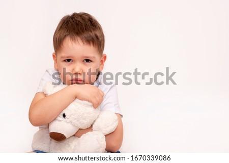 Sad child hugs a toy polar bear on a light background