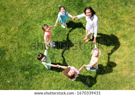 Overhead view female elementary teacher playing game of ring a roses with children on grass #1670339431