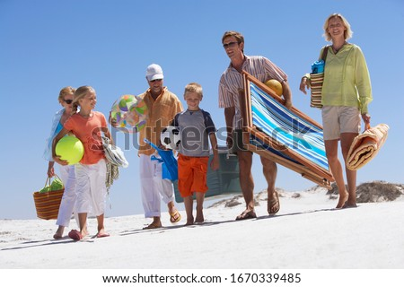 Three generation family walking on sandy summer vacation beach carrying deckchair bags towels and balls #1670339485