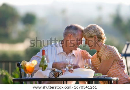 Loving mature couple eating at outdoor restaurant table #1670341261