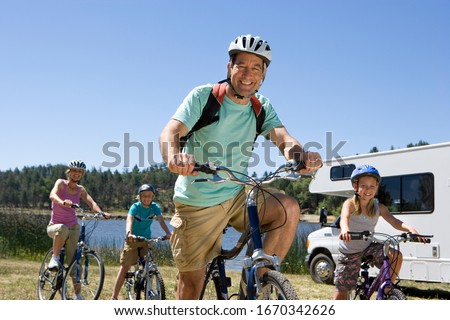 Family riding bikes in countryside on motor home vacation #1670342626