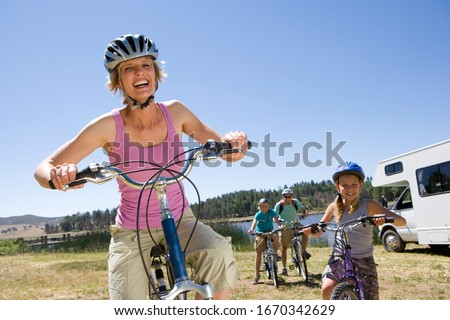 Family riding bikes in countryside on motor home vacation #1670342629