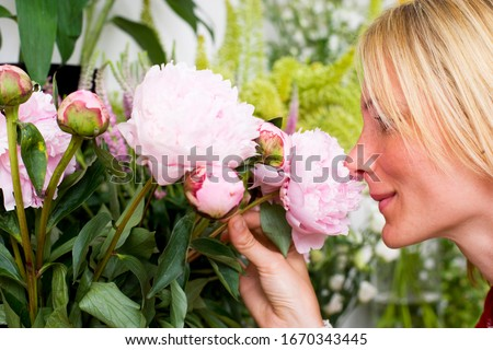 Woman smelling flowers in florists store #1670343445