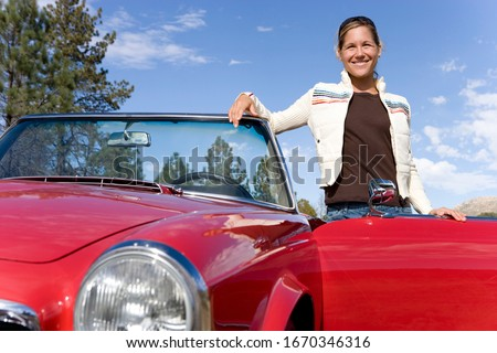Smiling mature woman next to classic convertible car at camera #1670346316