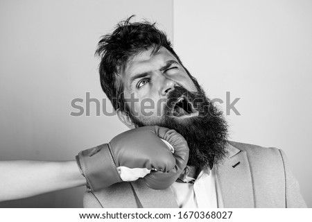 Teeth pain concept. Defenseless head. Suffering. Punch in face. Destroy beauty. Cosmetology and plastic surgery services. Strong punch. Hand in boxing glove punching bearded male face. Painful punch. #1670368027