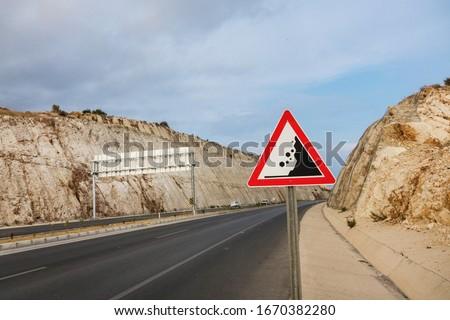 International traffic sign 'Falling rock' standing on highway road