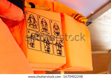 Orange life vests on a ship, closeup on the use instructions, detail How to put on, putting on a life jacket, shallow dof. Personal flotation device, information pictures, flotation suit, buoyancy aid