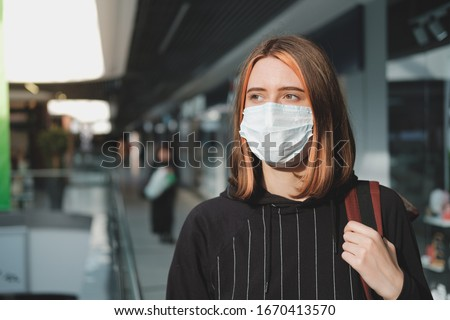 Woman in a protective face mask at a shopping mall. Coronavirus, COVID-19 spread prevention concept, responsible social behaviour of a citizen #1670413570