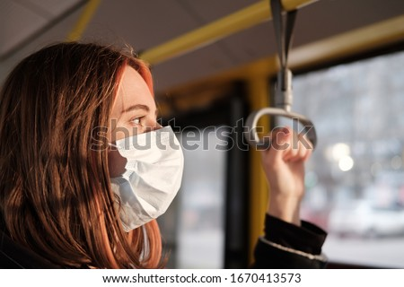 Commuter wears a protective mask in public transport. Coronavirus, COVID-19 spread prevention concept, responsible social behaviour of a citizen #1670413573