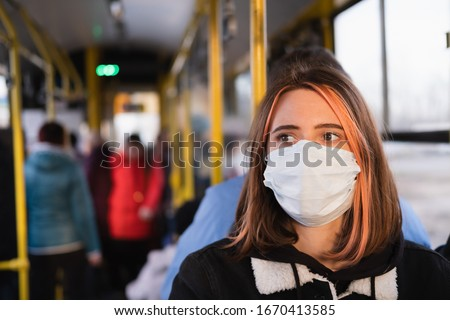 Young female adult commutes in a protective face mask. Coronavirus, COVID-19 spread prevention concept, responsible social behaviour of a citizen #1670413585