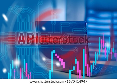 Work with the API. API logo on the background of the laptop. Concept - career programmer. Work in a web studio. Workplace web programmer. Charts as a symbol of financial app. Application programming