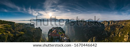 Aerial view of monastery Trinity and breathtaking pictures of valley and landmark canyon of Meteora at sunset, Kalambaka, Greece, shadows, twisted road, bridge, Mountains as columns