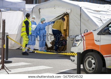 Alert pandemic Covid-19. Triage hospital field tent for the first AID, a mobile medical unit for patient infected with Corona Virus. Doctors with protective masks check the patiences at the entrance. #1670454532