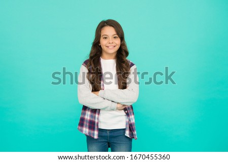 Confident beauty. little beauty. express positive emotions. happy small girl turquoise wall. cheerful schoolgirl has long curly hair. child wear trendy casual jacket. kid spring and autumn fashion. #1670455360