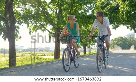 Young Caucasian couple smiles while riding bicycles down a scenic green avenue. Beautiful blonde girl and her handsome boyfriend riding their bikes along a picturesque sunlit park in the summertime. #1670463892