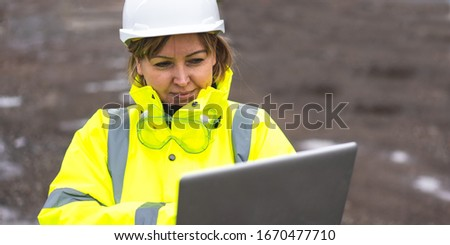 Woman architect inspecting site. Woman civil engineer close up. Young woman using laptop on construction site. Woman engineer developer holding laptop working Confident outdoors in construction site.