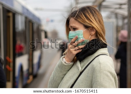 Sad Caucasian woman wearing sterile protective medical mask ill by the Covid-2019 Corona virus at public bus station in a European city street feeling bad looking down to the side people on background #1670515411