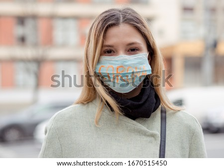 Girl with mask to protect her from Corona virus. Corona written on mask. Woman with mask standing in front of a clinic building. Beautiful blond haired girl with medical mask. Corona virus pandemic #1670515450