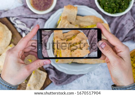 Woman hands take picture of food at home or cafe with smartphone. Phone photo of sauerkraut cabbage pie for blogging or social media. Vegan and vegetarian healthy diet.