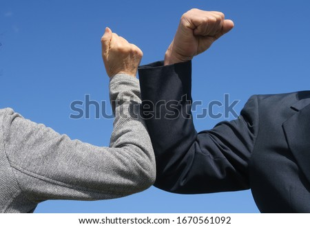 Elbow bumping. A new way of greeting to avoid the spread of coronavirus (COVID-19). Two people (a man and a woman) bump elbows instead of hug or handshake. New normal. Royalty-Free Stock Photo #1670561092
