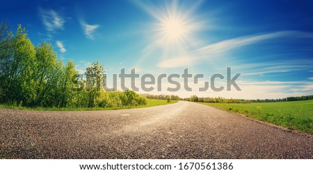 asphalt road panorama in countryside on sunny spring day Royalty-Free Stock Photo #1670561386