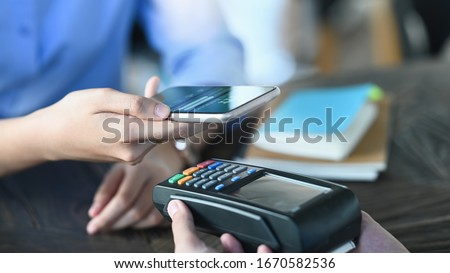 Cropped image of smart man's hands holding a smartphone and doing a payment by using a NFC technology at the Credit card reader that putting on cafe payment counter. Technology and Payment concept. #1670582536