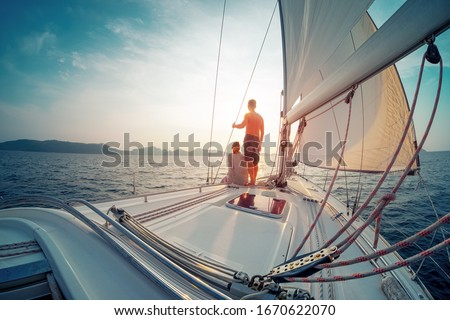 Young couple sailing in the tropical sea at sunset on their yacht #1670622070