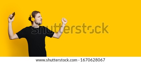 Caucasian man with beard and long hair is dancing on yellow background while listening to music through headphones #1670628067