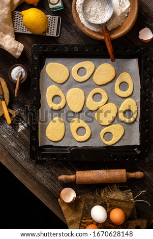 overhead shot of baked egg shaped easter cookies on baking tray on rustic wooden table with flour, eggs, butter, lemon. process of baking cookies. easter card #1670628148