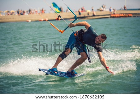 Professional kiter makes the difficult trick on a river. Kitesurfing Kiteboarding action photos man among waves quickly goes