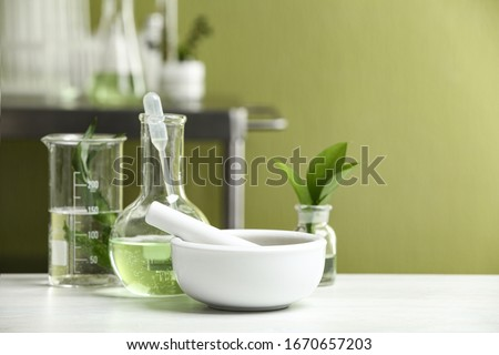 Mortar with pestle and natural ingredients on white table in cosmetic laboratory Royalty-Free Stock Photo #1670657203