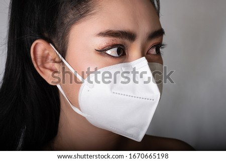 Close up of a woman putting on a respirator N95 mask to protect from airborne respiratory diseases as the flu covid-19 coronavirus ebola PM2.5 dust and smog, Safety virus infection concept Royalty-Free Stock Photo #1670665198