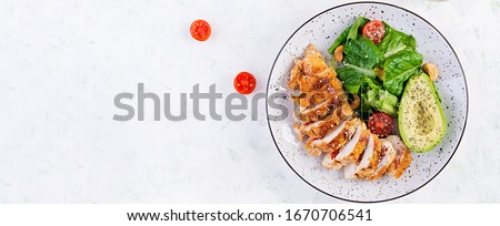 Trendy salad. Chicken grilled fillet with salad fresh tomatoes and avocado. Healthy food, ketogenic diet, diet lunch concept. Keto/Paleo diet menu. Top view, overhead, banner #1670706541