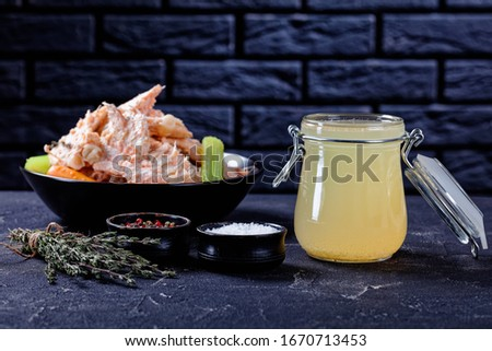 fish broth or stock of salmon in a glass jar on a concrete table with fish meat, bones  and veggies in a bowl at the background of a brick wall, horizontal view from above