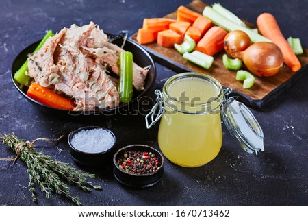 close-up of slow-cooked fish broth or stock of salmon in a glass jar on a concrete table with fish meat, bones  and veggies in a bowl