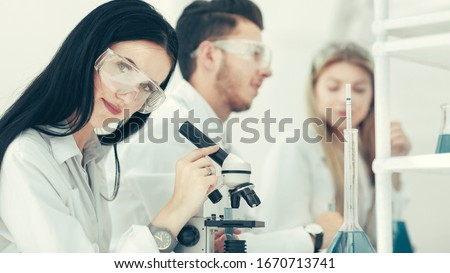 female scientist uses a microscope in the laboratory #1670713741