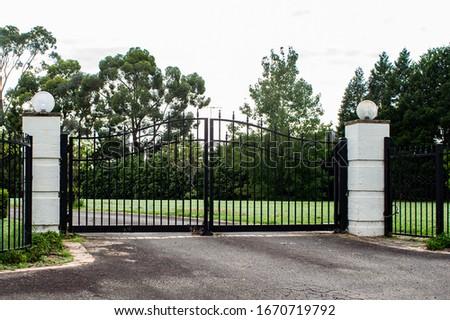 Black metal wrought iron driveway property entrance gates set in brick  Royalty-Free Stock Photo #1670719792
